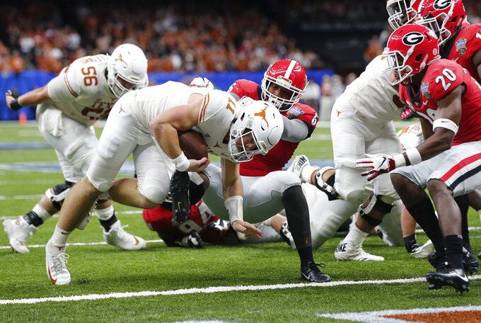 Texas quarterback Sam Ehlinger (11) crosses the goal line for a touchdown, as Georgia defensive back J.R. Reed (20) and others defend during the first half of the Sugar Bowl NCAA college football game in New Orleans, Tuesday, Jan. 1, 2019. (AP Photo/Gerald Herbert)