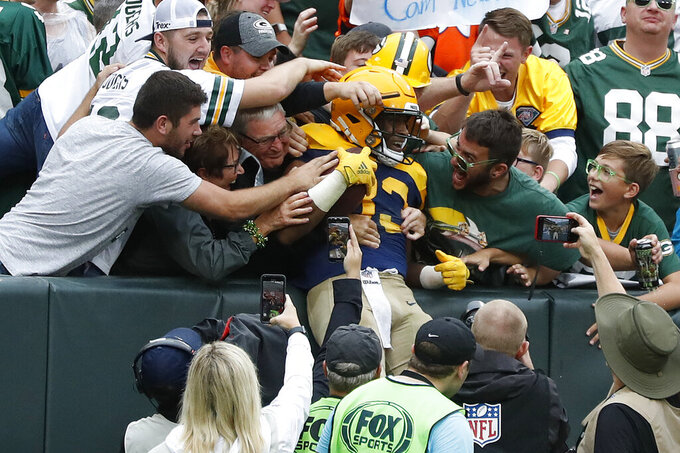 Green Bay Packers running back Aaron Jones is congratulated by fans after scoring during the second half of an NFL football game against the Denver Broncos, Sunday, Sept. 22, 2019, in Green Bay, Wis. (AP Photo/Matt Ludtke)
