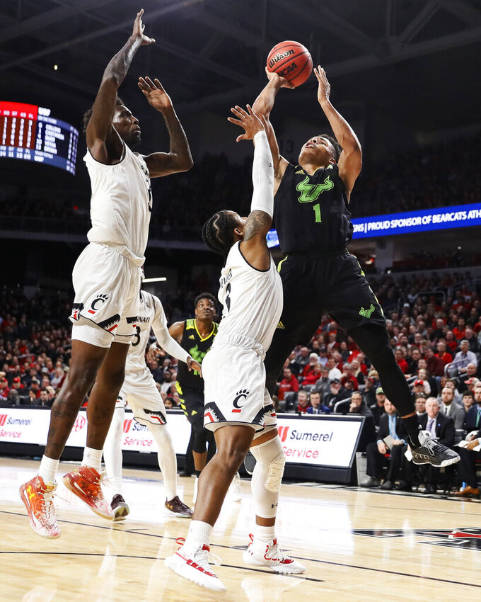 South Florida's Xavier Castaneda (1) shoots against Cincinnati's Justin Jenifer (3) in the second half of an NCAA college basketball game, Tuesday, Jan. 15, 2019, in Cincinnati. (AP Photo/John Minchillo)
