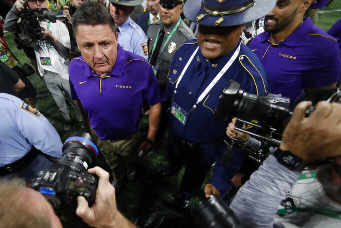 LSU head coach Ed Orgeron leaves the field after the Southeastern Conference championship NCAA college football game against Georgia, Saturday, Dec. 7, 2019, in Atlanta. LSU won 37-10. (AP Photo/John Bazemore)