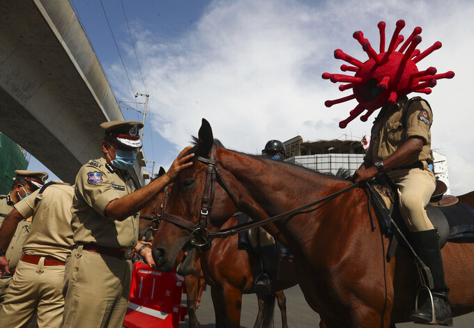 A policeman rides a horse wearing a virus-themed helmet during a COVID-19 awareness drive in Hyderabad, India, Tuesday, June 1, 2021. (AP Photo/Mahesh Kumar A.)