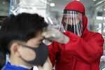 A barber wearing a protective suits and face shield to prevent the spread of the new coronavirus concentrates as he cuts the hair of a man at a barbershop in Manila, Philippines on Monday, June 8, 2020. Barbershops and beauty salons are now allowed to operate under strict health measures as the lockdown continues to ease in the capital. (AP Photo/Aaron Favila)