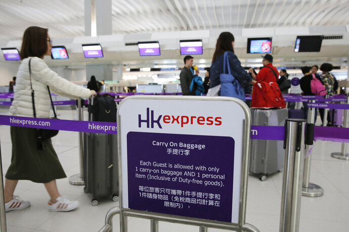FILE - In this March 26, 2019, file photo, passengers wait at the check-in counter of Hong Kong Express Airways at the Hong Kong International Airport. The airline Hong Kong Express has apologized Friday, Jan. 17, 2020 for having required some female passengers bound for the U.S. territory of Saipan to take pregnancy tests. (AP Photo/Kin Cheung, File)