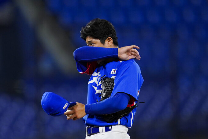 South Korea's Euilee Lee wipes his face during a semi-final baseball game against the United States at the 2020 Summer Olympics, Thursday, Aug. 5, 2021, in Yokohama, Japan. (AP Photo/Sue Ogrocki)