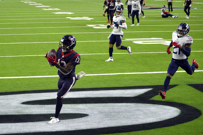 Houston Texans wide receiver Brandin Cooks (13) catches a touchdown pass as Tennessee Titans cornerback Malcolm Butler (21) defends during the second half of an NFL football game Sunday, Jan. 3, 2021, in Houston. (AP Photo/Eric Christian Smith)