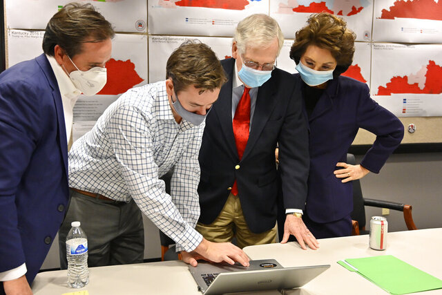 Republican Senate candidate Sen. Mitch McConnell, second from right, and his wife, Elaine Chao, right, look on as aides show him the election results in Louisville, Ky., Tuesday, Nov. 3, 2020. (AP Photo/Timothy D. Easley)