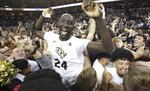 In this March 7, 2019, file photo, Central Florida center Tacko Fall (24) celebrates as fans storm the court after UCF defeated Cincinnati in an NCAA college basketball game in Orlando, Fla. Fall, at 7-foot-6 the tallest player in the game, at last gets to appear on the game's biggest stage when UCF opens the NCAA Tournament on the college basketball's biggest stage. (Stephen M. Dowell/Orlando Sentinel via AP, File)