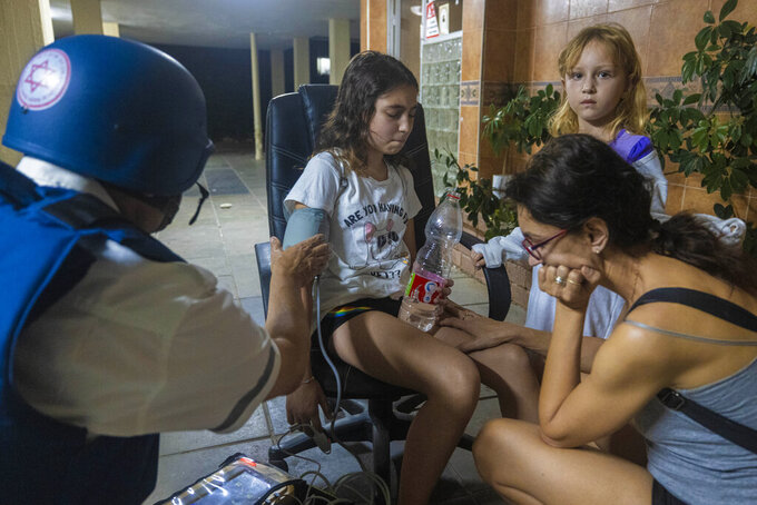 An Israeli paramedic checks the blood pressure of a young girl at residential building after it was hit by a rocket fired from Gaza Strip, in Ashkelon, southern Israel, Wednesday, May 12, 2021. (AP Photo/Tsafrir Abayov)