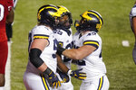 Michigan's Hassan Haskins (25) celebrates with Karsen Barnhart, left, and Ben Mason during the third overtime of an NCAA college football game against Rutgers on Saturday, Nov. 21, 2020, in Piscataway, N.J. Michigan won 48-42. (AP Photo/Frank Franklin II)