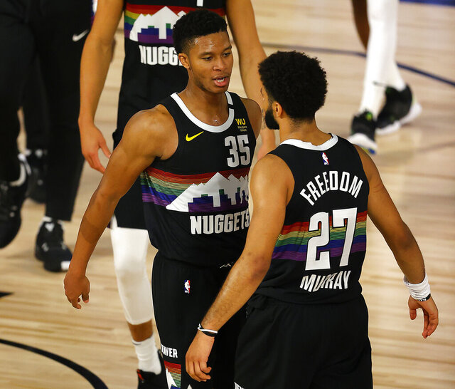 Jamal Murray, right, of the Denver Nuggets and teammate PJ Dozier, left, celebrate after their win over Utah Jazz in of Game 5 of an NBA basketball first-round playoff series, Tuesday, Aug. 25, 2020, in Lake Buena Vista, Fla. (Mike Ehrmann/Pool Photo via AP)
