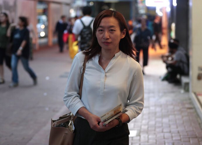In this photo taken Thursday, Nov. 7, 2019, district council candidate Cathy Yau walks during her campaign at Causeway Bay in Hong Kong. Yau. a former police officer, grew exasperated as police used more force to quell the unrest. She quit the force in July after 11 years and is running in Sunday's district polls that are widely expected to deliver a decisive victory for the six-month-old movement seeking democratic reforms in the semi-autonomous Chinese territory. (AP Photo/Dita Alangkara)