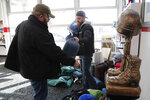 In this Wednesday, Jan. 8, 2020 photo, Larry Mortimer, left, helps Tim Fitzgerald load sleeping bags for the homeless at the Bedford Township Veterans Center in Temperance, Mich. Mortimer, a 36-year-old veteran of the Iraq War, did not vote in 2016. He now considers himself undecided. But this past week pushed him closer to Trump, he said, because the president made America look tough. (AP Photo/Carlos Osorio)