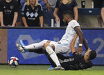 Sporting Kansas City forward Daniel Salloi (20) pulls down Minnesota United defender Romain Metanire (19) during the first half of an MLS soccer match in Kansas City, Kan., Thursday, Aug. 22, 2019. (AP Photo/Orlin Wagner)