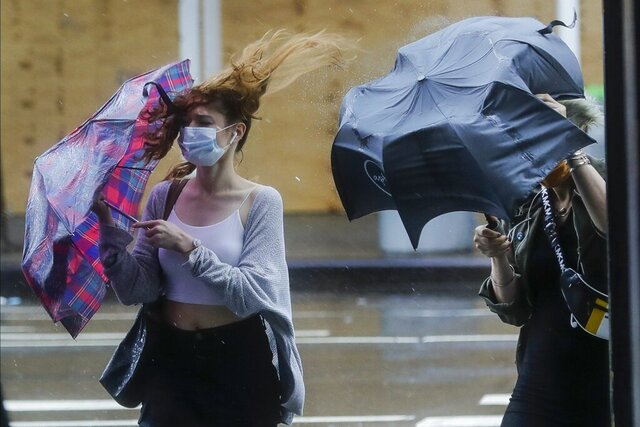Pedestrians struggle to control their umbrellas due to inclement weather brought about by Tropical Storm Fay, Friday, July 10, 2020, in New York. Beaches closed in Delaware and rain lashed the New Jersey shore as fast-moving Tropical Storm Fay churned north on a path expected to soak the New York City region. (AP Photo/Frank Franklin II)