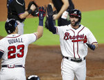 Atlanta Braves' Dansby Swanson gets a high-five from Adam Duvall after hitting a home run during the second inning in Game 2 of a baseball National League Division Series against the Miami Marlins Wednesday, Oct. 2020, in Houston. (Curtis Compton/Atlanta Journal-Constitution via AP)
