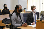 NFL football player Richard Sherman, center, sits at a hearing at King County District Court with his attorney Cooper Offenbecher, right, as his wife Ashley Sherman looks on, Friday, July 16, 2021, in Seattle. Prosecutors in Washington state have charged Sherman, who has played for the Seattle Seahawks and the San Francisco 49ers, after police said he drunkenly crashed his SUV in a construction zone and tried to break into his in-laws' home. (AP Photo/Ted S. Warren)
