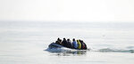 A group of people thought to be migrants arrive in an inflatable boat at Kingsdown beach after crossing the English Channel, near Dover, Kent, England, Monday, Sept. 14, 2020. (Gareth Fuller/PA via AP)