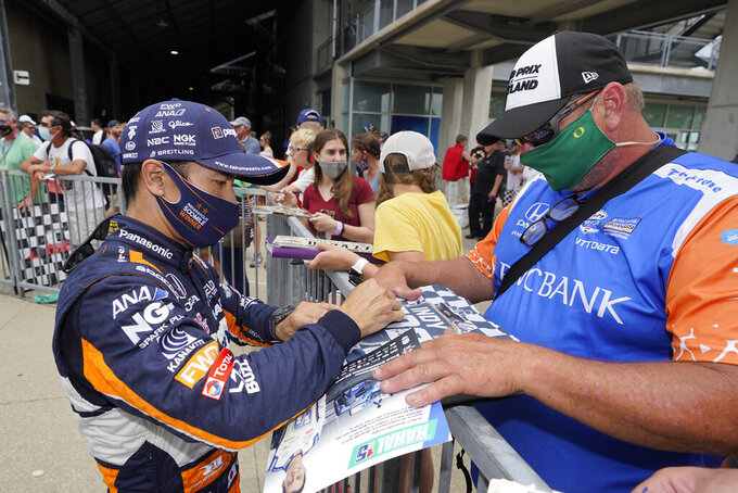 Takuma Sato, of Japan, signs an autograph for a fan during qualifications for the Indianapolis 500 auto race at Indianapolis Motor Speedway, Saturday, May 22, 2021, in Indianapolis. (AP Photo/Darron Cummings)