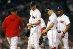 Boston Red Sox manager Alex Cora, left, comes to the mound to relieve Chris Sale, center, during the fifth inning of a baseball game against the Los Angeles Dodgers in Boston, Saturday, July 13, 2019. (AP Photo/Michael Dwyer)