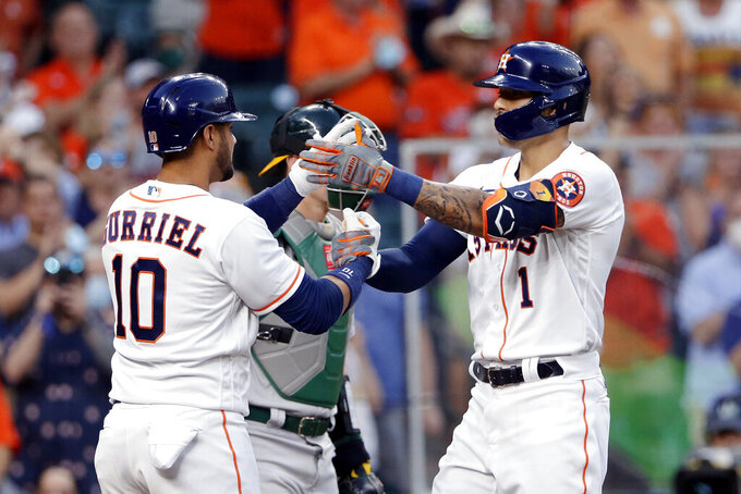 Houston Astros' Yuli Gurriel (10) and Carlos Correa (1) celebrate at the plate after Correa's home run during the second inning against the Oakland Athletics in a baseball game Thursday, April 8, 2021, in Houston. (AP Photo/Michael Wyke)