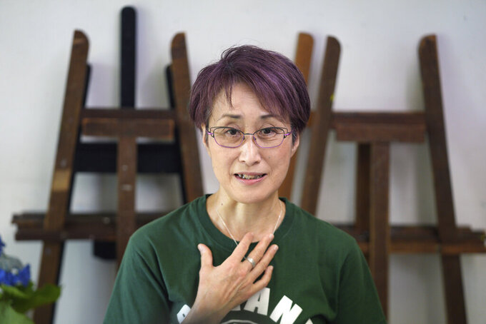 """Japanese artist Miwako Sakauchi speaks about her art work for an art exhibition """"Declaration of the end of Olympic games"""" in Chiba near Tokyo Thursday, June 10, 2021. """"What I can do instead of going to (anti-Olympics) protests is to use my expertise in art,"""" said Sakauchi of her motivation to produce the paintings. She has never participated in street protests or incorporated political issues into her abstract paintings in the past, but the Tokyo Olympics have been a tipping point. (AP Photo/Eugene Hoshiko)"""