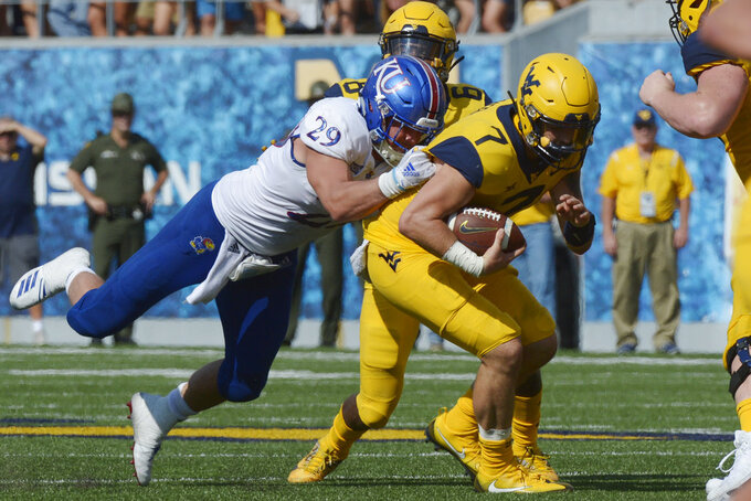 West Virginia quarterback Will Grier (7) is tackled by Kansas linebacker Joe Dineen Jr. (29) during the second half of an NCAA college football game against Kansas in Morgantown, W. Va., Saturday Oct. 6, 2018. (AP Photo/Craig Hudson)