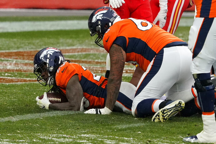 Denver Broncos running back Melvin Gordon, left, scores a touchdown during the second half of an NFL football game against the Kansas City Chiefs, Sunday, Oct. 25, 2020, in Denver. (AP Photo/Jack Dempsey)