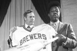 FILE - Milwaukee Brewers manager Del Crandall, left, and Henry Aaron display Aaron's new Brewers jersey and a bat during a news conference in Milwaukee to announce signing Aaron, in this Nov. 14, 1974, file photo. Crandall, a star catcher who played on two Milwaukee Braves teams that reached the World Series in the 1950s before managing the Milwaukee Brewers and Seattle Mariners, has died. He was 91. Crandall's son Bill said his father was surrounded by family members as he died from circumstances of Parkinson's disease Wednesday, May 5, 2021, at Mission Viejo, California.(AP Photo/Paul Shane, File)
