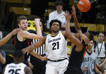 Colorado forward Evan Battey, center, passes the ball after getting trapped by Oregon State forwards Kylor Kelley, left, and Alfred Hollins in the first half of an NCAA college basketball game Sunday, Jan. 5, 2020, in Boulder, Colo. (AP Photo/David Zalubowski)