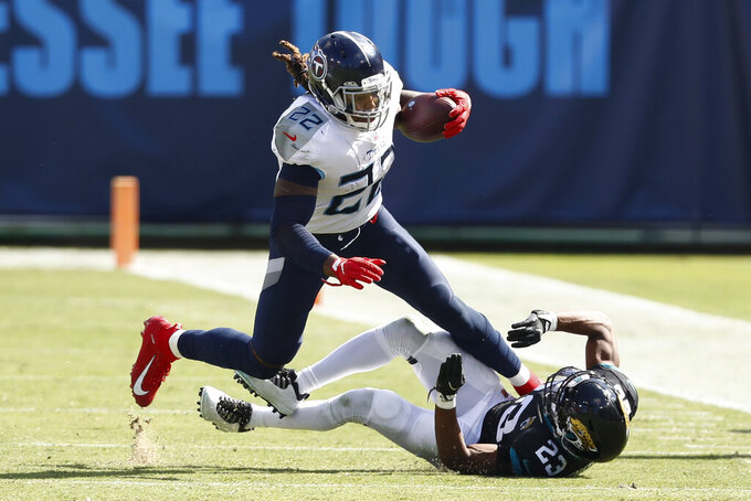 Tennessee Titans running back Derrick Henry (22) runs past Jacksonville Jaguars cornerback C.J. Henderson (23) in the second half of an NFL football game Sunday, Sept. 20, 2020, in Nashville, Tenn. (AP Photo/Wade Payne)