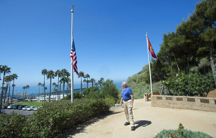 Former San Clemente Mayor Wayne Eggleston looks back after lowering the U.S. flag to half-staff at Park Semper Fi in San Clemente, Calif., on Friday, July 31, 2020. An amphibious assault vehicle carrying multiple Marines and a Navy sailor sank near a military-owned island off the coast of Southern California on Thursday. (Paul Bersebach/The Orange County Register via AP)