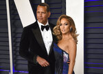 """FILE - Alex Rodriguez, left, and Jennifer Lopez arrive at the Vanity Fair Oscar Party in Beverly Hills, Calif. on Feb. 24, 2019. Lopez and Rodriguez told the """"Today"""" show Thursday, April 15,2021, in a joint statement that they are calling off their two-year engagement. (Photo by Evan Agostini/Invision/AP, File)"""