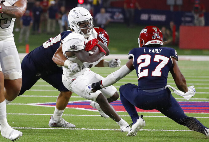 Fresno State defenders wrap up UNLV wide receiver Tyleek Collins during the second half of an NCAA college football game in Fresno, Calif., Friday, Sept. 24, 2021. (AP Photo/Gary Kazanjian)