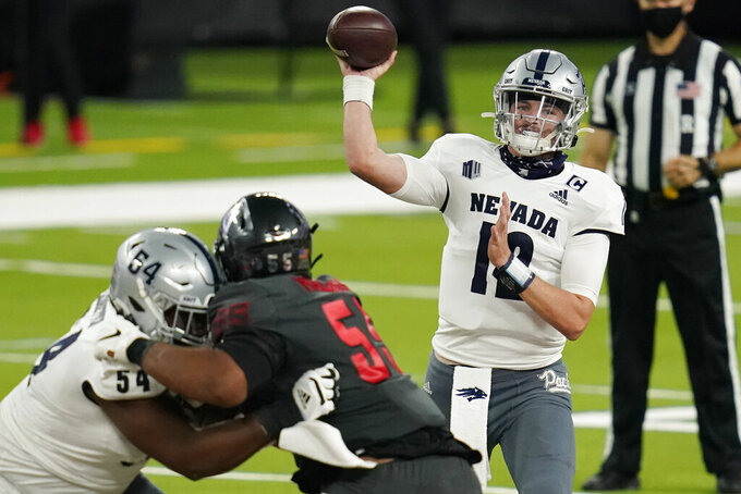 Nevada quarterback Carson Strong (12) throws against UNLV during the first half of an NCAA college football game Saturday, Oct. 31, 2020, in Las Vegas. (AP Photo/John Locher)