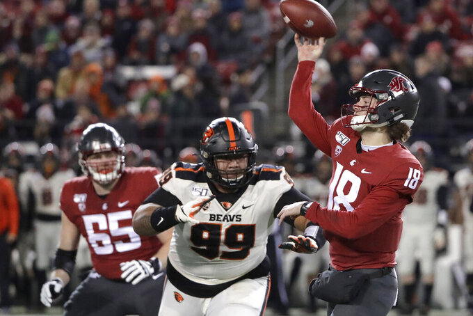 Washington State quarterback Anthony Gordon, right, passes under pressure from Oregon State defensive lineman Elu Aydon (99) during the first half of an NCAA college football game Saturday, Nov. 23, 2019, in Pullman, Wash. (AP Photo/Ted S. Warren)
