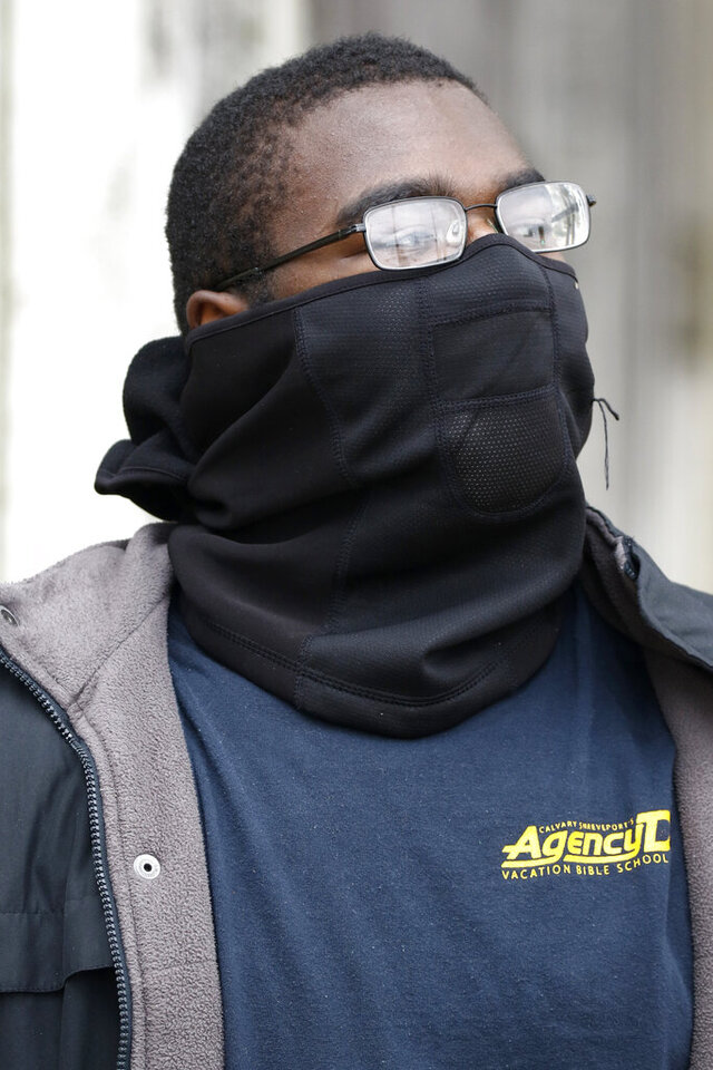 Darius James said a fear of contracting the coronavirus and the lack of available protective facemarks in central Mississippi forced him to improvise using a ski scarf for protection Thursday, March 19, 2020 in Jackson, Miss. (AP Photo/Rogelio V. Solis)