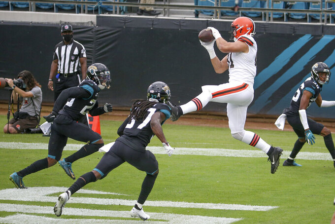 Cleveland Browns tight end Austin Hooper, right, catches a touchdown pass in front of Jacksonville Jaguars safety Jarrod Wilson, left, and cornerback Tre Herndon, center, during the first half of an NFL football game, Sunday, Nov. 29, 2020, in Jacksonville, Fla. (AP Photo/Stephen B. Morton)