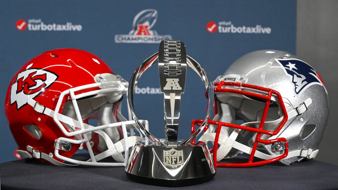 The Lamar Hunt Trophy stands between helmets of the Kansas City Chiefs and the New England Patriots, during a news conference Wednesday, Jan. 16, 2019, in Kansas City, Mo. The Chiefs are scheduled to play the Patriots for the NFL football AFC championship Sunday. (John Sleezer/The Kansas City Star via AP)