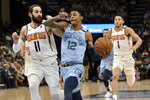 Memphis Grizzlies guard Ja Morant (12) drives ahead of Phoenix Suns guards Ricky Rubio (11) and Devin Booker (1) in the first half of an NBA basketball game Sunday, Jan. 26, 2020, in Memphis, Tenn. (AP Photo/Brandon Dill)