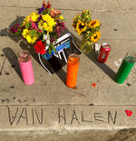 Legend has it that the name Van Halen, seen etched in concrete at the corner of Allen and Villa in Pasadena, Calif., was done by brothers Eddie and Alex Van Halen when they lived in Pasadena, Calif., in their younger years, where a sidewalk memorial has begun after Eddie's death from cancer at age 65, Tuesday, Oct. 6, 2020. Guitar virtuoso Eddie Van Halen is being mourned across the world of music. Artists from Lenny Kravitz to Kenny Chesney are honoring Van Halen, whose blinding speed, control and innovation propelled his band into one of hard rock's biggest groups. (AP Photo/Andrew Dalton)