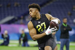 FILE - In this Feb. 28, 2020, file photo, Wisconsin running back Jonathan Taylor runs a drill at the NFL football scouting combine in Indianapolis. (AP Photo/Michael Conroy, File)