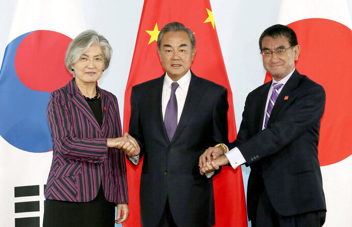 Chinese Foreign Minister Wang Yi, center, holds hands of his South Korean counterpart Kang Kyung-wha, left, and Japanese counterpart Taro Kono for photos ahead of their meeting in Beijing Wednesday, Aug. 21, 2019. (Kyodo News via AP)