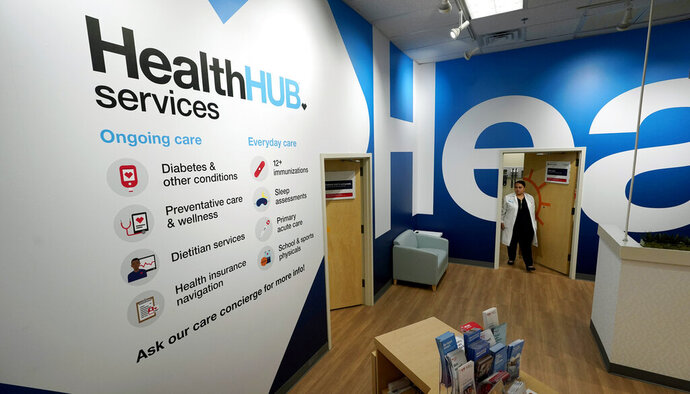 In this Thursday, May 30, 2019 photo, family Nurse Practitioner Serena Lopez exits an exam room at the new HealthHUB inside a CVS store in Spring, Texas. HealthHUB locations offer a broader range of health care services, new product categories, digital tools and on-demand health kiosks, trusted advice and personalized care. (AP Photo/David J. Phillip)