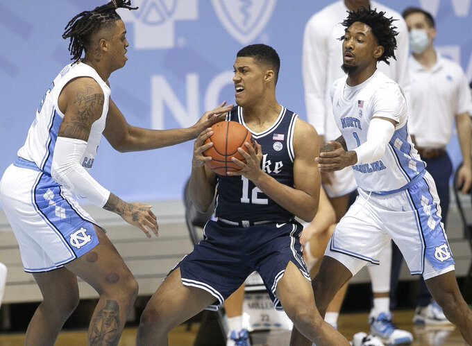 Duke's Patrick Tape (12) is trapped by North Carolina's Armando Bacot (5) and Leaky Black (1) during the first half of an NCAA college basketball game Saturday, March 6, 2021, in Chapel Hill, N.C. (Robert Willett/The News & Observer via AP)