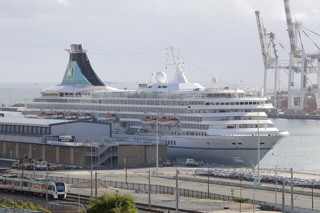 This Friday, March 27, 2020, photo shows the cruise ship Artania docked at Fremantle harbour in Fremantle, Australia. More than 800 cruise ship passengers and crew are heading home to Germany on chartered flights while 41 others infected with the coronavirus have been admitted to an Australian hospital after an argument over where they should be treated among local medical personnel. (Richard Wainwright/AAP Image via AP)