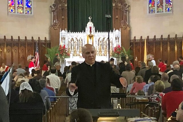 FILE - In this June 9, 2019 photo, Father Eduard Perrone conducts a choir during mass at Assumption of the Blessed Virgin March Parish in Detroit. The Detroit priest who said he was defamed by a police officer in an investigation of alleged sexual abuse has settled a lawsuit against her for $125,000. Perrone said he doesn't care about the money but wants to be reinstated at Assumption Grotto Church, a Catholic parish he had led for 25 years until he was removed by the Detroit Archdiocese in 2019. (AP Photo/Paul Sancya, File)