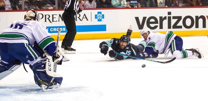 Seattle Kraken's Riley Sheahan tries to get off a shot in the first period as he slides toward the goal during an NHL preseason hockey game against the Vancouver Canucks Sunday, Sept. 26, 2021, in Spokane, Wash. (Dean Rutz/The Seattle Times via AP)