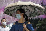 People wearing face masks to help curb the spread of the coronavirus walk by a decoration outside a shopping mall in Beijing, Sunday, June 28, 2020. China has extended COVID-19 tests to newly reopened salons amid a drop in cases while South Korea continues to face new infections as it eases social distancing rules. (AP Photo/Andy Wong)