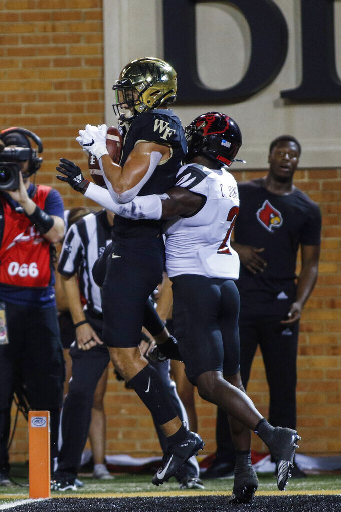 Wake Forest wide receiver Sage Surratt, left, catches a 12-yard pass for a touchdown against Louisville defensive back Chandler Jones during the first half of an NCAA college football game in Winston-Salem, N.C., Saturday, Oct. 12, 2019. (AP Photo/Nell Redmond)