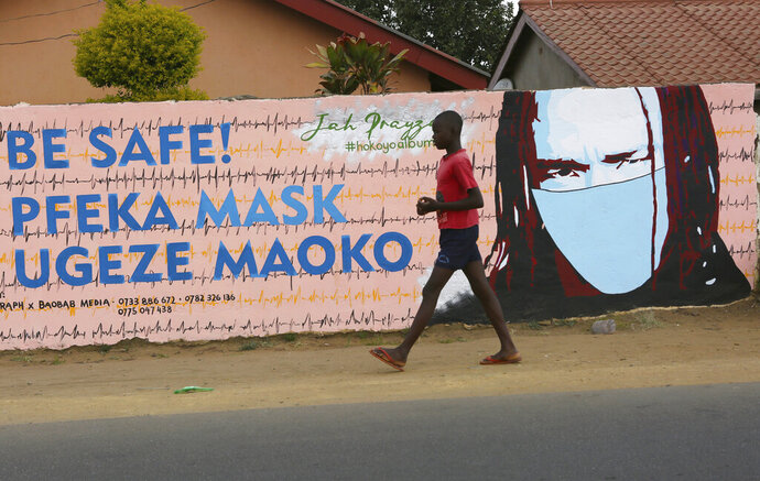 A young boy walks past a wall with graffiti urging people to wear face masks in Harare, Thursday, May, 28, 2020. Manhunts have begun after hundreds of people, some with the coronavirus, fled quarantine centres in Zimbabwe and Malawi while authorities worry they will spread COVID-19 in countries whose health systems can be rapidly overwhelmed. (AP Photo/Tsvangirayi Mukwazhi)